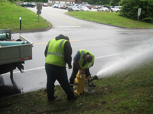 Men flushing fire hydrant